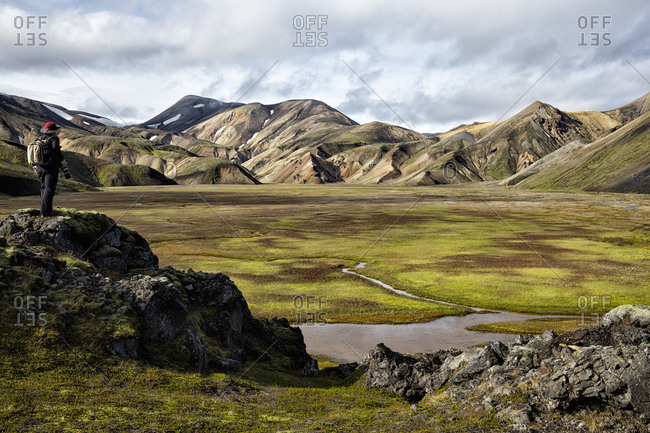 Man overlooking mountains and a plain at Landmannalaugar, Iceland