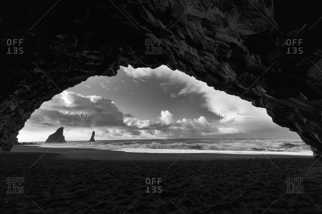 Basalt sea stacks viewed from the mouth of a seaside cave on the Icelandic coast
