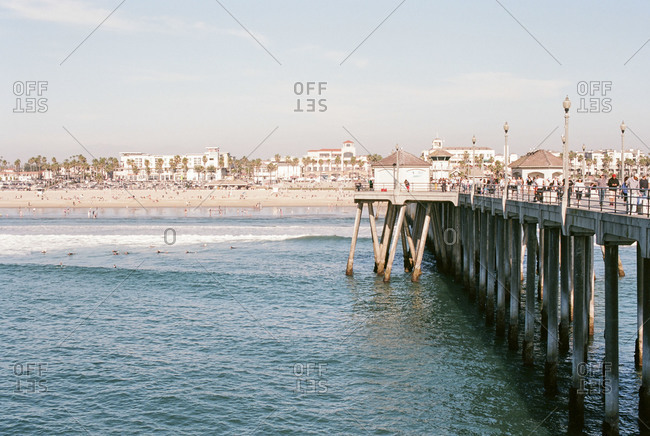 People swimming near a pier on a beach