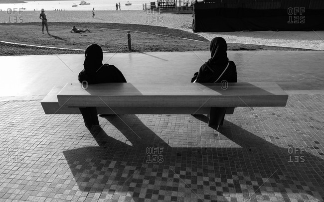 Women sitting near beach in United Arab Emirates