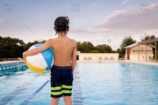 Back view of young boy holding a beach ball at pool