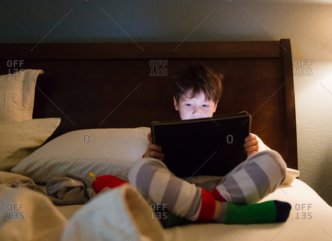 Boy in striped pajamas and green socks watching tablet on bed