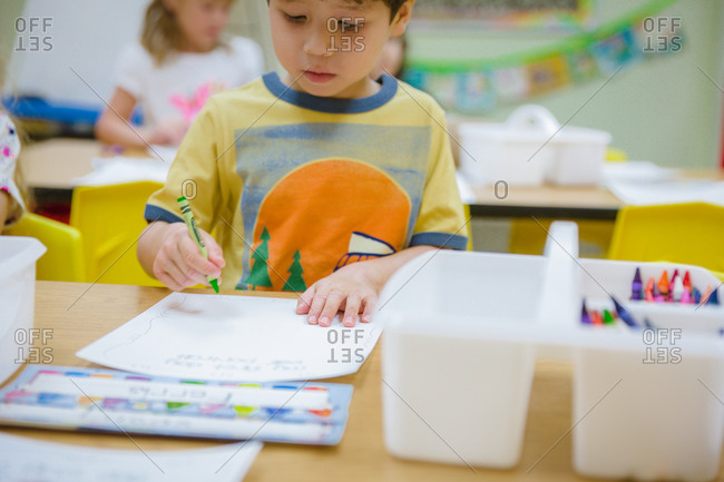 Young boy drawing with crayons at classroom table