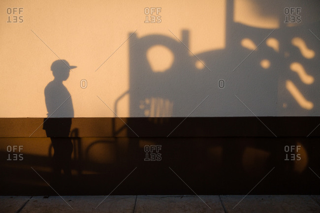 Shadow of boy on playground structure on wall at sunset