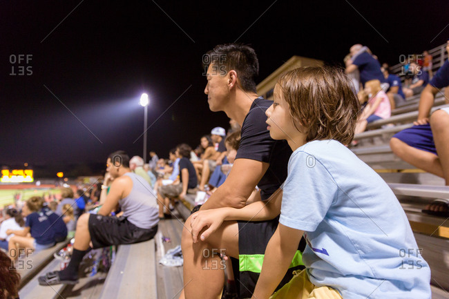 Man watching football game with son under the lights on bleachers