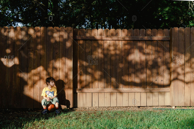 Young boy sitting on basketball against fence in backyard