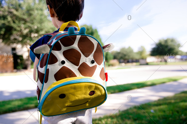 Young boy wearing a giraffe backpack heads off to school