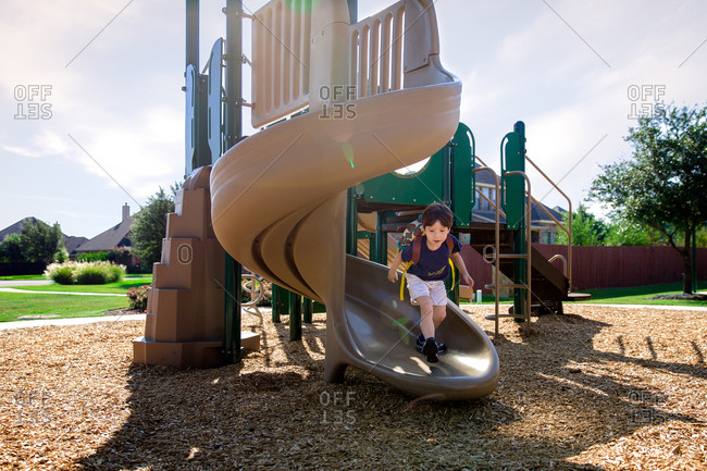 Young boy wearing backpack running down playground slide