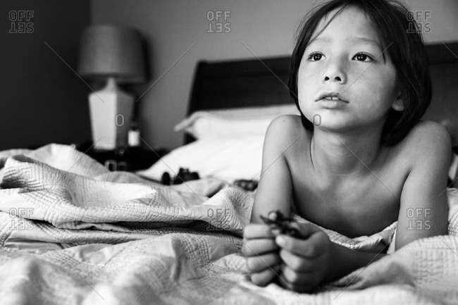 Shirtless young boy lying on bed with toy