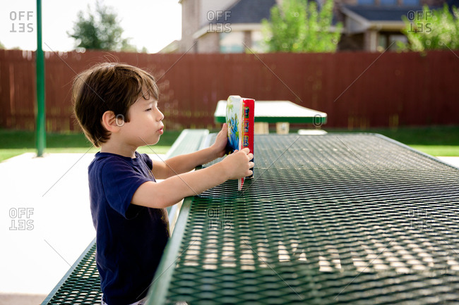 Young boy reading book at playground table