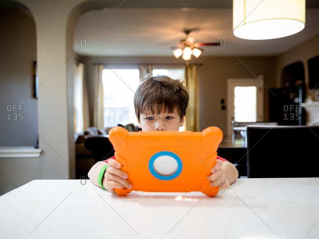 Young boy at kitchen table using tablet