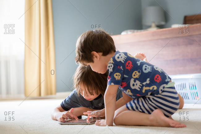 Two brothers playing game on tablet computer on bedroom carpet
