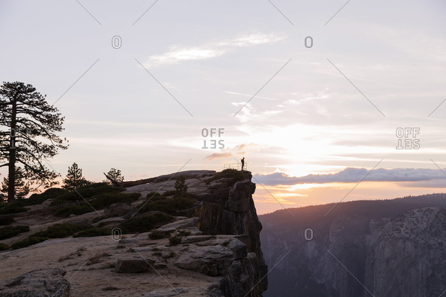 Man standing on a cliff overlooking a canyon