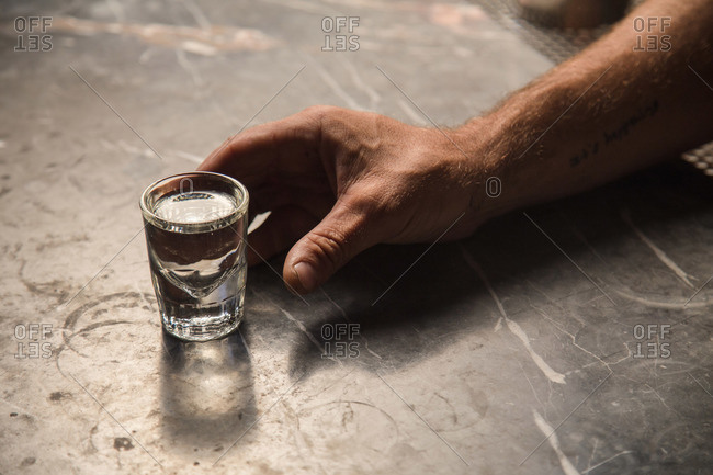 Man's hand reaching for a shot glass