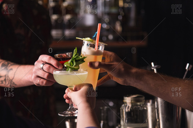 Three people clinking together beverage glasses