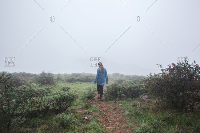 Woman walking on a nature trail in the fog