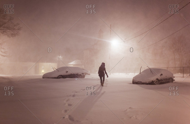 Woman walking through a snow-covered parking lot at night