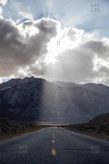 Sun shining on a highway over mountains
