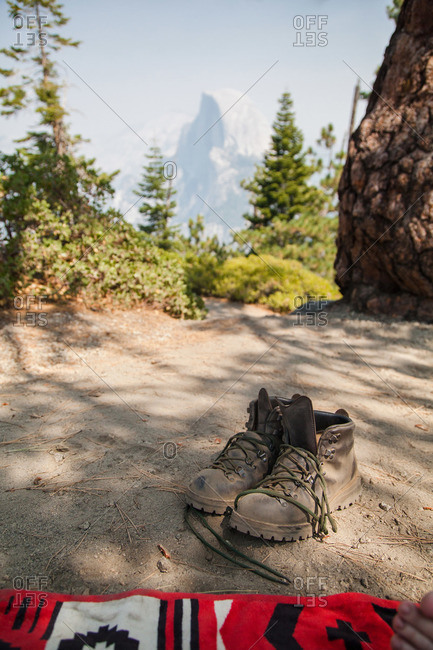 Person's empty hiking boots with mountains in the distance