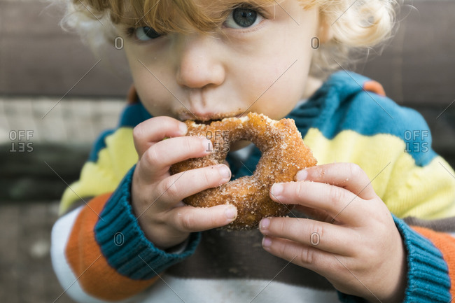 A boy in a striped sweater eats a donut