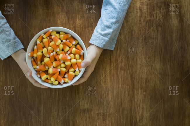A child reaches for a bowl of candy corn