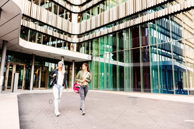 Young women exiting a modern urban building