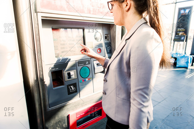 Young woman using a ticket kiosk in Malmo Central Station in Sweden