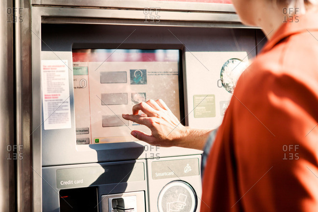 Using touch screen ticket machine in Malmo Central Station in Sweden