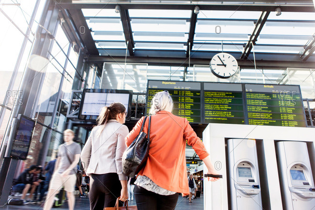 Women looking at train schedules at in Malmo Central Station in Sweden
