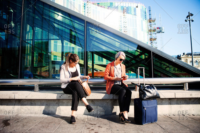 Women wait with luggage at a train station in Malmo, Sweden