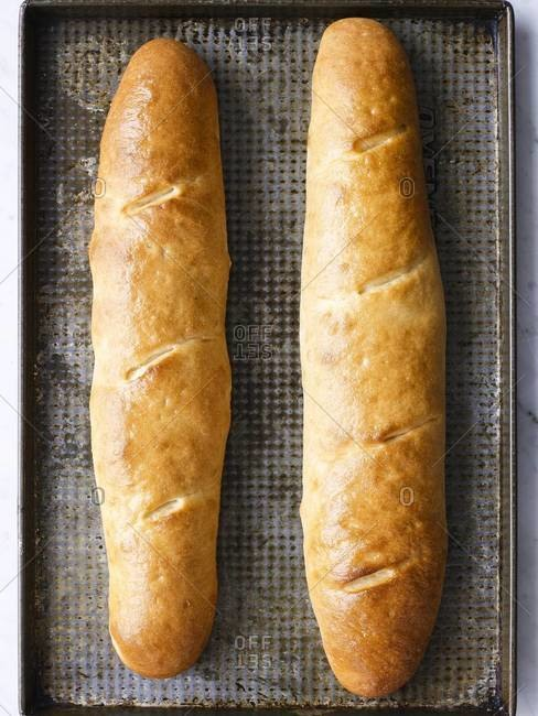 French baguettes on a metal baking tray
