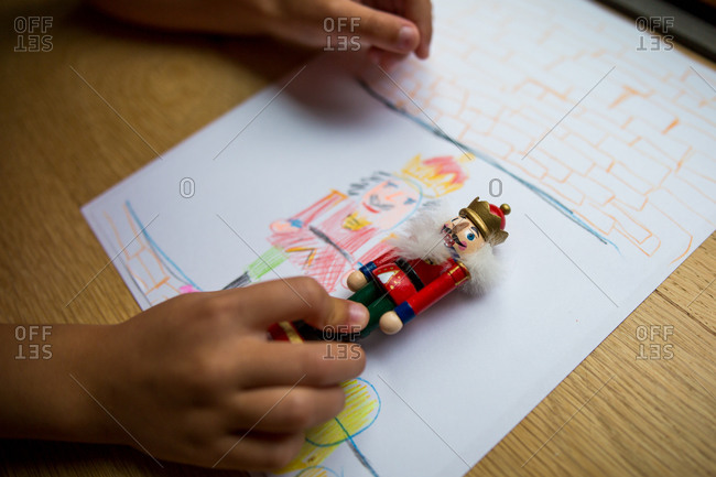 Child holding a small nutcracker figure up to drawing of the nutcracker