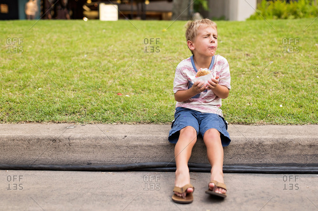 Young boy experiencing brain freeze while eating ice cream treat