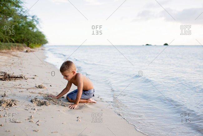 Young boy playing in sand at water's edge on beach
