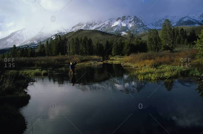 Man fly fishing in river with reflection of mountains