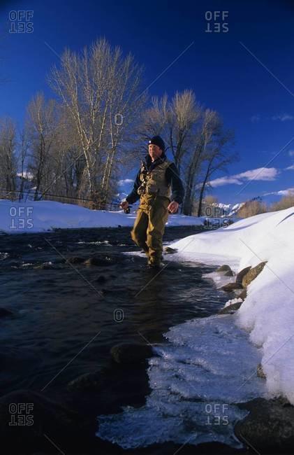 Fisherman walking in river in winter