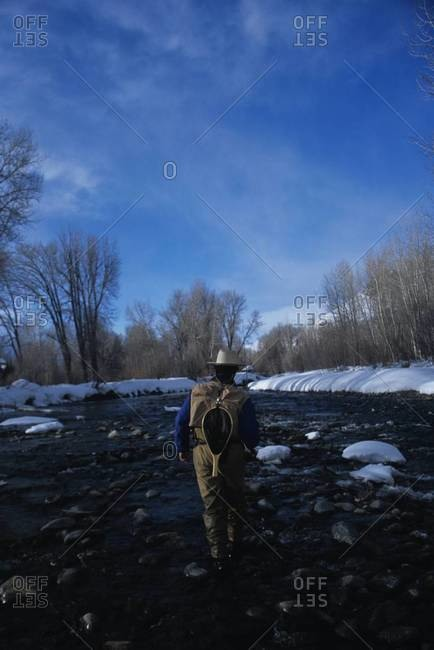 Back view of fisherman walking in river in winter