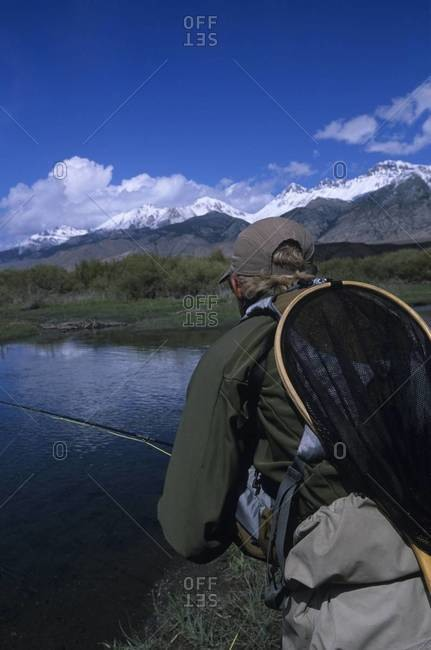 Back view of fisherman with rod at river in mountain landscape