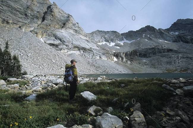 Backpacker with fishing pole in wilderness landscape