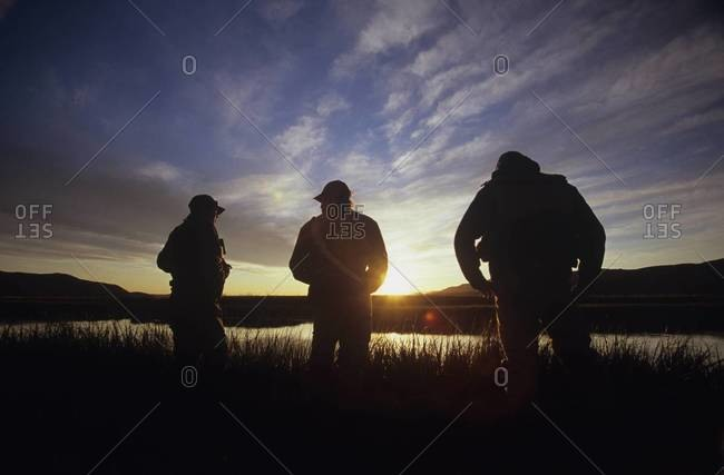 Back view of three outdoorsmen silhouetted by river at dusk