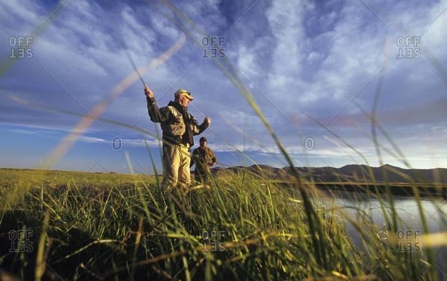 Two men fishing at creek at dusk