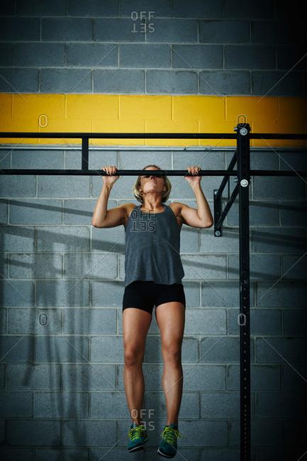 Woman doing chin-ups at a gym