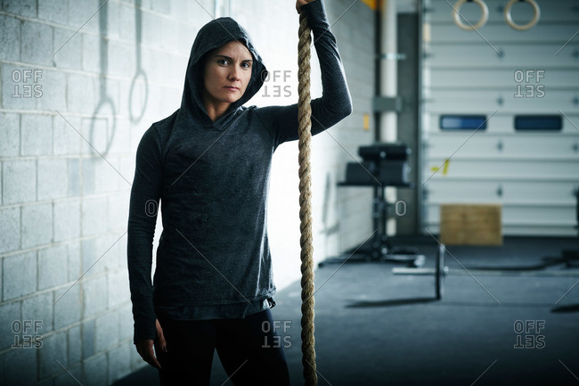 Woman with a climbing rope in a crossfit gym