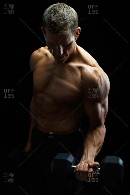 Studio shot of a man lifting a dumbbell
