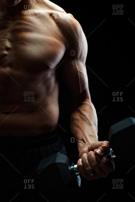 Muscular man lifting a hand weight