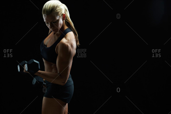 Muscular woman lifting hand weights