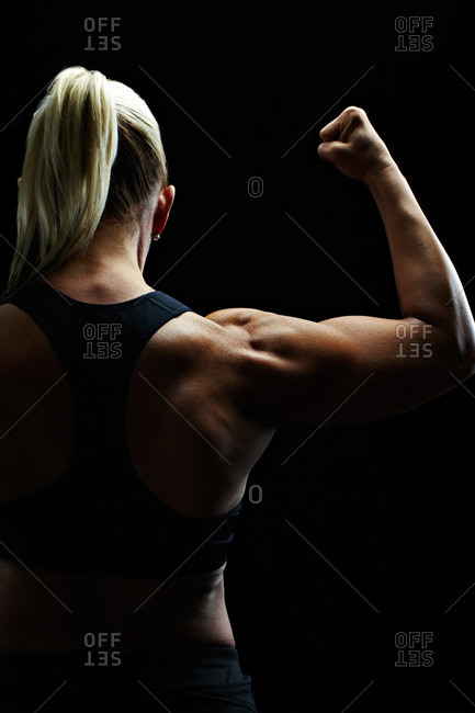 Studio shot of a woman flexing her muscles