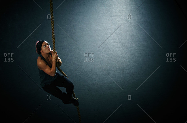 Woman climbing a rope during crossfit training