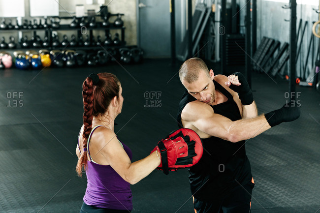 Man and woman practice boxing at a gym