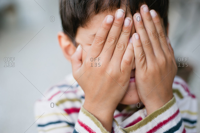 Young boy covering his face with his hands
